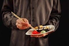 De handen van de mens in een zwart overhemd houden een plaat met sushi op zwarte achtergrond stock fotografie