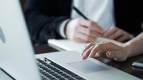 De handen van de mens schrijven en het vrouwenwerk bij PC bij bureau