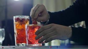 De handen van de mens verfraaien met bessen en sinaasappelschil verfrissende drank in groot glas op lijst in lichte mist stock footage