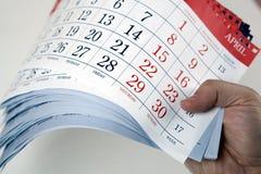 De handen van mensen houden de bladen van de kalender Stock Afbeelding