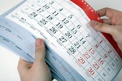 De handen van mensen houden de bladen van de kalender Stock Fotografie