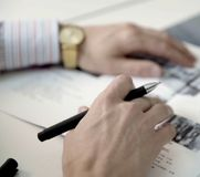 De handen van mensen met gouden horloges houden een het schrijven pen over het document stock foto