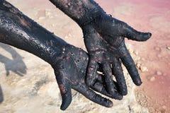 De handen van mensen smeerden zwarte modder Close-up Bij de Zoutmeren van meerlas, Torrevieja spanje Stock Foto's