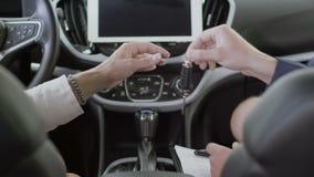 De handen van mensenschokken tijdens succesvolle overeenkomst van het kopen van auto en koper tonen de sleutels stock video