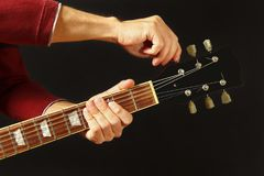 De handen van musicus stemt de gitaar op donkere achtergrond royalty-vrije stock afbeeldingen