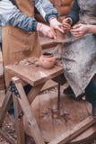 De handen van pottenbakker helpen waterkruik op aardewerkwiel maken Stock Foto's