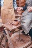 De handen van pottenbakker helpen waterkruik op aardewerkwiel maken Royalty-vrije Stock Afbeeldingen