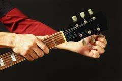 De handen van rotsgitarist stemt de gitaar op donkere achtergrond stock afbeelding