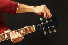 De handen van rotsmusicus stemt de gitaar op donkere achtergrond royalty-vrije stock fotografie