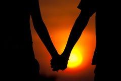 De handen van silhouettenparen op zonsondergang Royalty-vrije Stock Fotografie