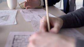 De handen van twee mannelijke architecten, die de de bouwblauwdrukken in bureau verbeteren, sluiten omhoog