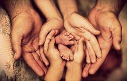 De handen van vader, moeder, dochter houden kleine voetenbaby Vriendschappelijke gelukkige familie Stock Afbeeldingen
