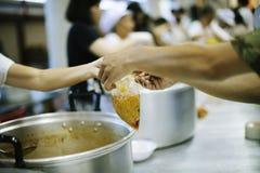De handen van Vluchtelingen ontvangen Humoristisch Liefdadigheidsvoedsel: Het Concept Voedseltekort stock foto