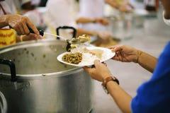 De handen van vluchtelingen zijn geholpen door liefdadigheidsvoedsel honger verminderen: het concept filantropie royalty-vrije stock foto's
