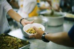 De handen van vluchtelingen zijn geholpen door liefdadigheidsvoedsel honger verminderen: het concept filantropie stock foto's