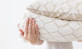 De handen van vrouw die modern beige bedlinnen houden stapelen zich, witte muurachtergrond op royalty-vrije stock foto