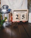 De handen van de vrouw houden houten kalender met 25 december-datum op de donkere houten achtergrond Nieuw jaar en Kerstmisconcep stock afbeelding