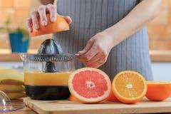 De handen van de vrouw houdt een grapefruit half en maakt sap stock afbeelding