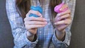 De handen van de vrouw kneden, drukken en rekken een roze en blauw slijm uit Vrouwenspelen met slijm stock videobeelden
