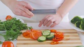 De handen van de vrouw met een smartphone nemen beelden van verse die groenten voor salade, op een scherpe raad worden gesneden stock video