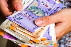 De handen van de vrouw met gloednieuwe Indiër 50, 100, 200, 500, 2000 Roepiesbankbiljetten