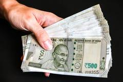 De handen van de vrouw met nieuwe Indische 500 Roepiesbankbiljetten