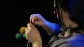 De handen van de vrouw op een zwarte achtergrond breit op cirkelnaalden van gele draad stock video
