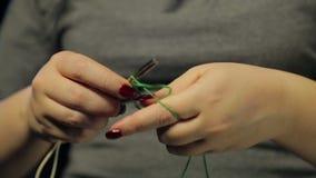 De handen van de vrouw op wijzerplaten zwarte als achtergrond op spokes van een lijn van groene draad stock videobeelden