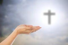 De handen van vrouwen die bidden over vertroebelden het kruis op hemelbackgro Royalty-vrije Stock Afbeelding
