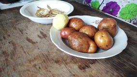 De handen van vrouwen maken gepelde aardappels schoon stock video