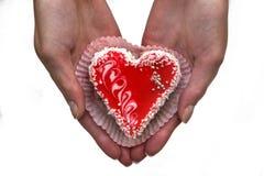 De handen van vrouwen met een hart gevormde cake stock foto's