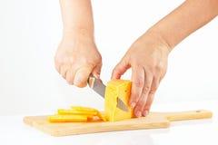 De handen van vrouwen met een mes gesneden kaas op een scherpe raad Stock Fotografie