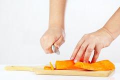 De handen van vrouwen met een mes hakt wortel op een scherpe raad royalty-vrije stock afbeeldingen