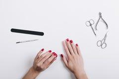 De handen van vrouwen met een rode manicureschaar en een nagelvijl op een wh royalty-vrije stock afbeeldingen