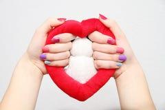 De handen van vrouwen met gekleurde spijkers Stock Foto