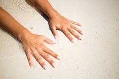 De handen van vrouwen op het strandzand bij de oceaan Stock Afbeeldingen