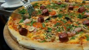 De handen van vrouwen snijden een stuk smakelijke verse pizza met Beierse worsten, paddestoelen, bacon, tomaten, greens af Dichte stock videobeelden
