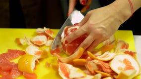 De handen van vrouwen snijden de gepelde grapefruit in stukken stock video