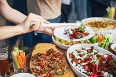 De handen van vrouwen stapelen zich op een maaltijd in een plaat van lunch Het concept voeding buffet Voedsel diner Het concept h Royalty-vrije Stock Foto's