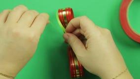 De handen van vrouwen verbinden de vorm van een spatie van rood lint met groene band om een gift te maken buigen Groene Achtergro stock footage