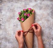 De handen van vrouwen verpakken een boeket van rozen in document royalty-vrije stock fotografie