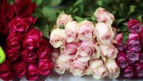 De handen van vrouwen zijn nemen roze Rozen bij storefront stock video