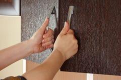 De handen van vrouwen zijn open de kastdeuren stock fotografie