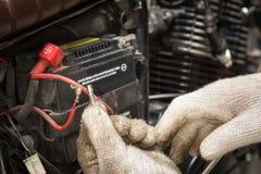De handen van de werktuigkundige die zekering in motorfiets vervangen en sele stock fotografie