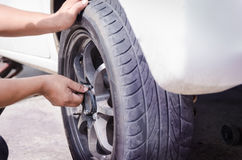 De handen van werktuigkundige nemen de noot van autowiel op en halen aan Stock Foto's