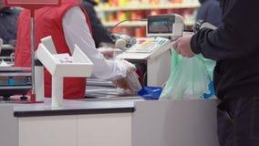 De handen van de winkelarbeider bij voedingsmiddelen cashdesk controle in supermarkt stock videobeelden