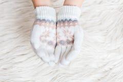 De handen van de winterkinderen ` s zijn wit in vuisthandschoenen op een witte bontachtergrond hygge De handen houden Royalty-vrije Stock Foto's