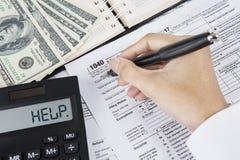 De handen van zakenman dienen belastingsvorm in stock afbeeldingen