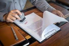 De handen van zakenman stempelen op document document om de overeenkomst van het handelsinvesteringencontract goed te keuren stock afbeeldingen