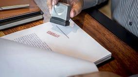 De handen van zakenman stempelen op document document om de overeenkomst van het handelsinvesteringencontract goed te keuren royalty-vrije stock afbeeldingen